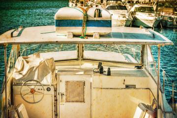 white boat in Alghero harbor in vintage effect