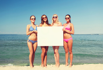group of smiling women with blank board on beach