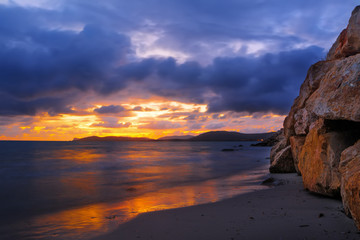rocks and sand in Alghero shore at sunset