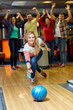 happy young woman throwing ball in bowling club - 79905490