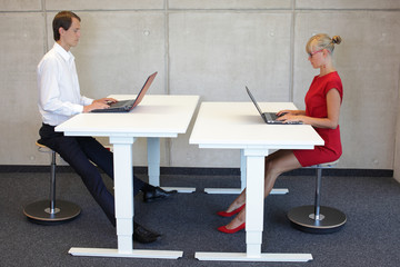 Business people - co workers in correct sitting posture at desks