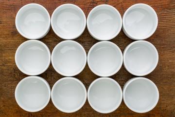 dozen of empty white tasting bowls