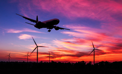 silhouette air plane flying on wind turbine farm at dusk