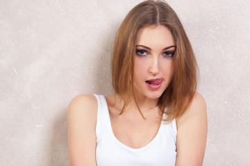 the self-assured girl seductively licks lips