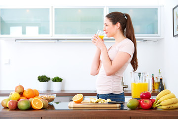 Young woman drinking a glass of orange Juice in the kitchen.