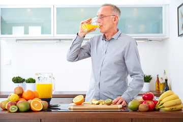 Mature man drinking orange Juice in the kitchen