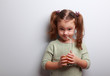 Funny emotion kid girl drinking juice from grass and looking