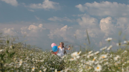 little girl with balloons runs through the blooming summer field