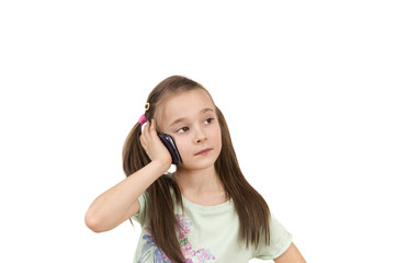 portrait of a young pig-tailed girl using mobile phone isolated