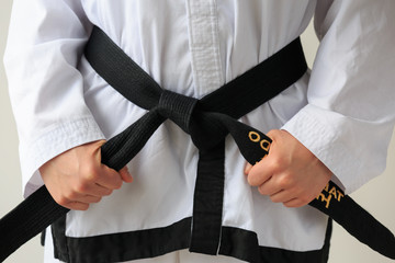 Taekwon-do woman with black belt and getting ready for training.