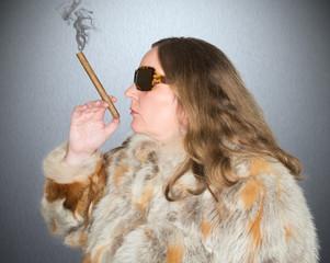 Frau mit Pelzmantel raucht eine Zigarre
