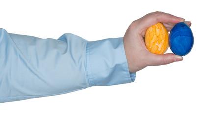 Frauenarm hält zwei gefärbte Eier der Hand