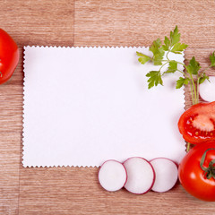 Vegetables and white sheet of paper on a wooden background