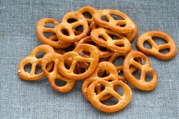 Heap of fresh Wheat salt pretzels on hessian linen fabric cloth