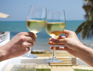 Man and woman clanging wine glasses with white wine