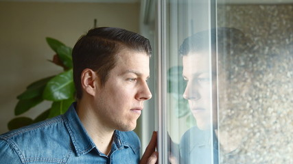 Man at home looking outside and smile into camera