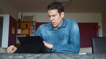 man at home with tablet and bad news