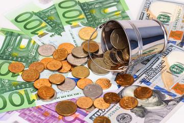 купюры евро, доллары и опрокинутое ведро с российскими деньгами