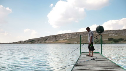 young man fishing on the jetty by the lake in summer
