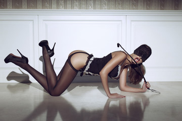 Sexy woman kneeling on the floor with whip