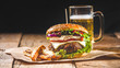 Fresh and juicy hamburger on a paper pad with a beer on a wooden