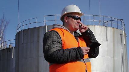 Happy worker talking on cell phone near oil tank