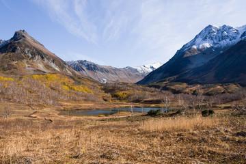 Lake in mountain valley. Autumn, first snow.