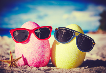 Two easter eggs with sunglasses on ocean beach –retro style
