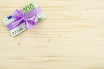 Hundred euro bill with pink bow on wooden table