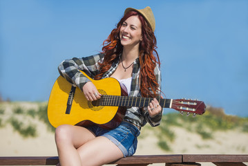 Pretty and young woman playing a guitar