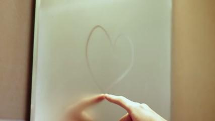 Man finger drawing a heart on sweaty mirror