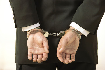 Hands of caucasian businessman in handcuffs.