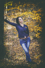 Vintage portrait of beautiful girl in jeans leaning in autumn fo
