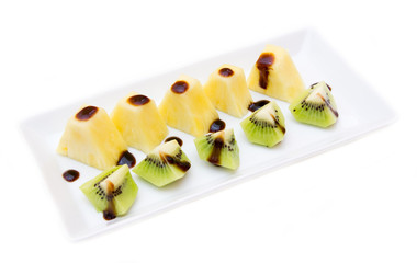Pineapple and kiwi with balsamic vinegar on white background