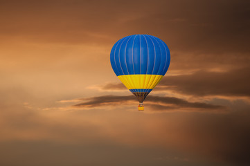 Yellow blue Hot Air Balloon in Flight on sunset sky background