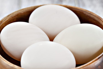 Duck eggs in brown wooden bowl