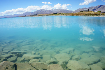 Natural turquoise Lake Tekapo and rocky edge