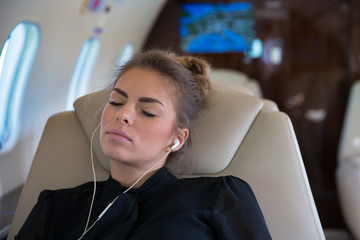 Business woman in a corporate jet relaxing and listening to musi