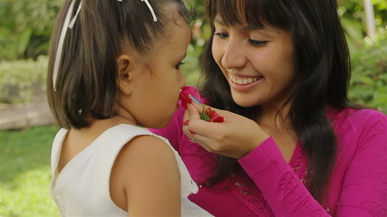 Girl and Mom Smelling Flower