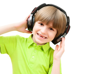 The small boy is listening to music, isolated on white