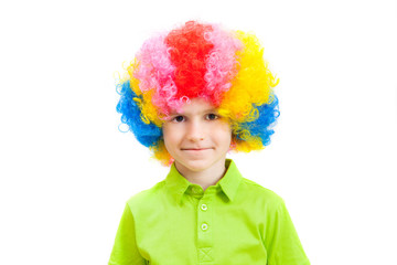 cute little boy in a multi-coloured clown wig