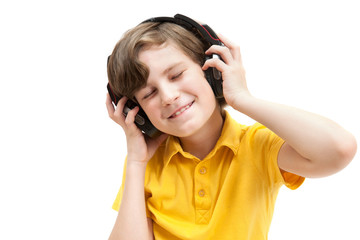 Happy boy listens music with headphones, isolated on white