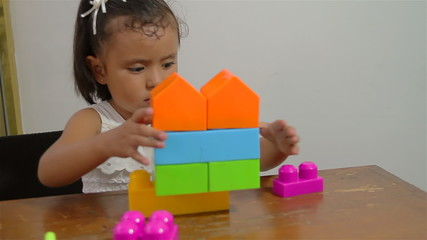Little Girl Learning to Stack Blocks