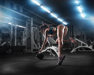 fitness brunette girl training back with dumbbell at gym