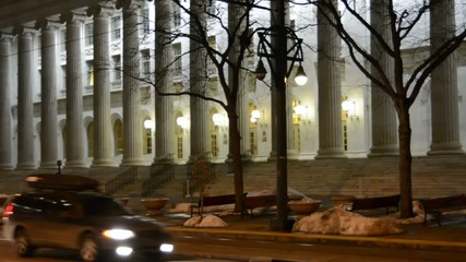 Pan across courthouse columns at night