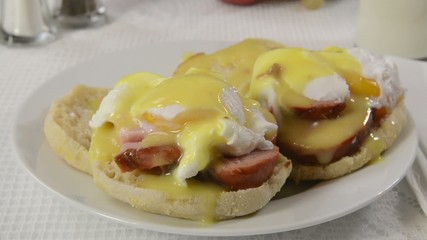 A plate of eggs benedict being served