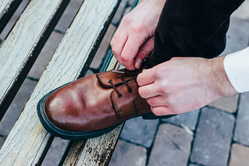 Man tying the laces on the brown boots.