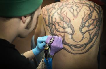 Tattooer does a tattoo