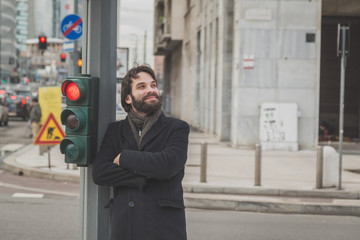 Young handsome bearded man posing in the city streets