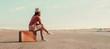Leinwanddruck Bild - Traveler girl sitting on a suitcase on road